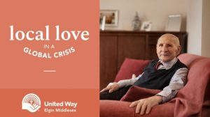 elderly man sits in a chair_local love logo